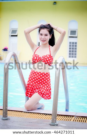 Beautiful girl in swimming suit at swimming pool