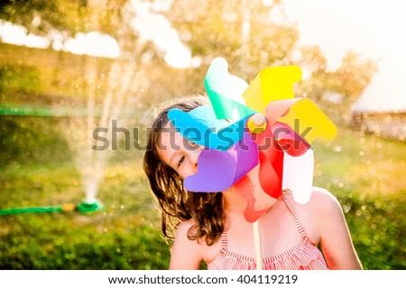 Beautiful girl in swimsuit hiding behind pinwheel, summer garden - stock photo