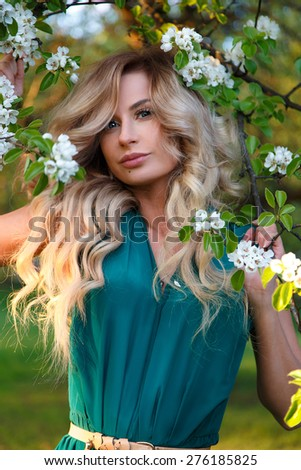 Beautiful girl in the apple blossoms.A spring image of beautiful young woman at apple tree flowers blossoms background. - stock photo