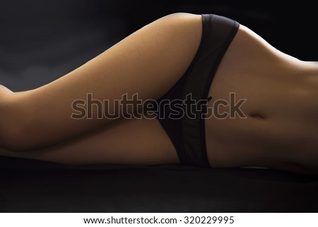 Beautiful girl in the black underwear, abdominal features. - stock photo