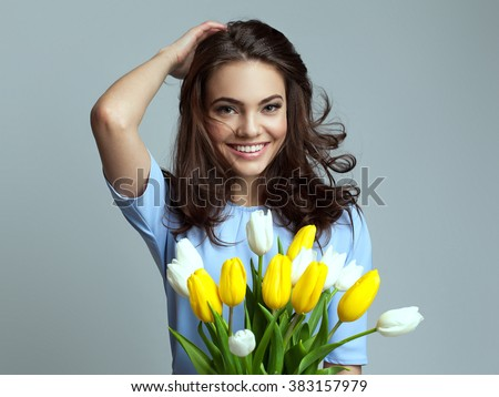 Beautiful girl in the blue dress with flowers tulips in hands on a light background