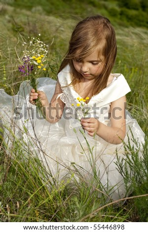 Beautiful girl in the clothes of bride on the field with the field flowers - stock photo