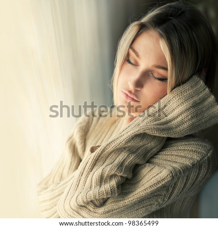 beautiful girl in the face at the window - stock photo