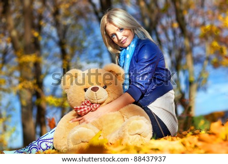 beautiful girl in the fall leaves with a teddy bear