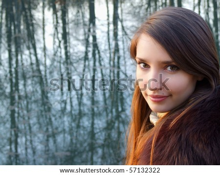 Beautiful girl in the fur coat in front of the lake - stock photo