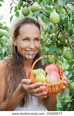 Beautiful girl in the garden with apples and pears in the crib - stock photo