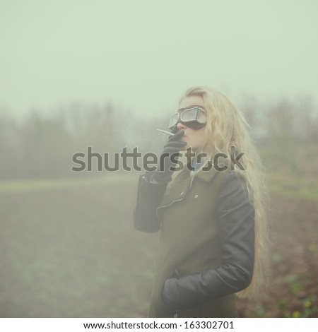 beautiful girl in the image of a vintage aviator with a cigarette - stock photo