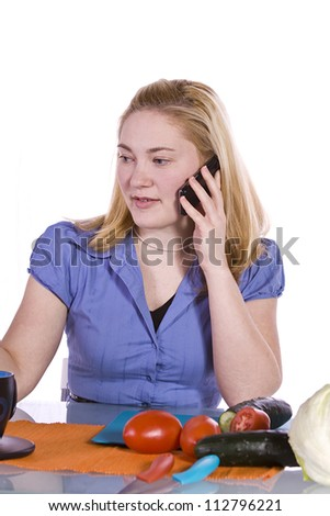 Beautiful Girl in the Kitchen Cutting Tomatoes and Cucumber While Talking on the Phone - stock photo