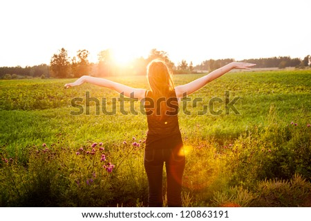 Beautiful girl in the meadow enjoying the sun - stock photo