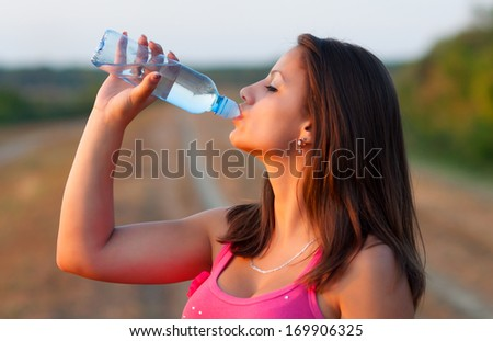 Beautiful girl in the nature drinking water. - stock photo