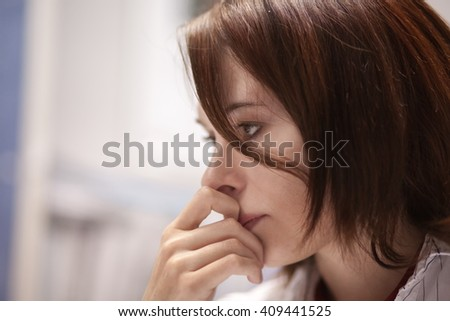 Beautiful girl in the office sitting in a chair and thinks about something - stock photo