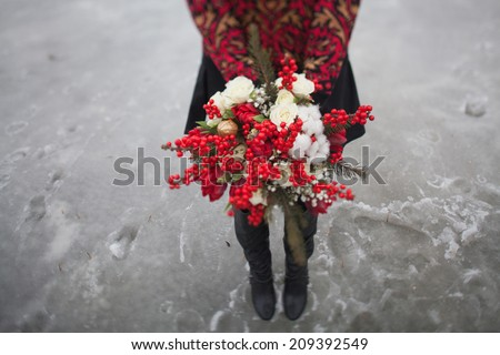 beautiful girl in the park in winter,  with a bouquet of red flowers - stock photo