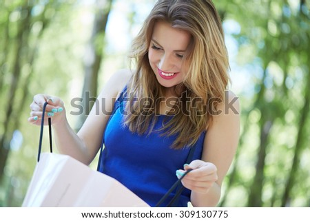 beautiful girl in the park looks into shopping bags