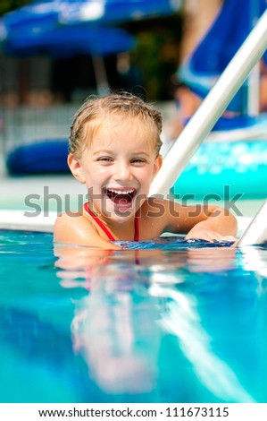 beautiful girl in the pool looks in a camera