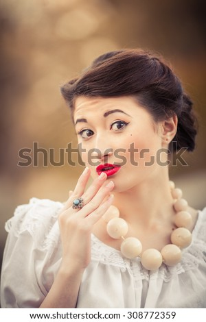 Beautiful girl in the style of pinup, closeup, bright red lipstick, expressive facial expressions - stock photo