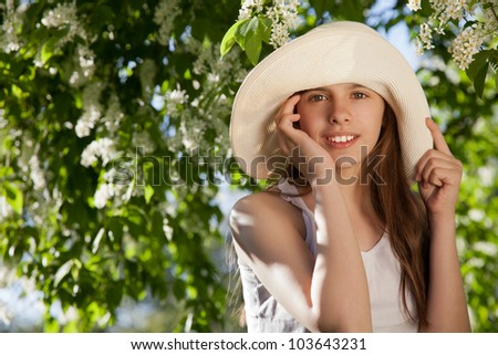 beautiful girl in the white hat near the cherry blossoms - stock photo