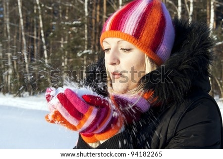 beautiful girl in the winter blows the snow - stock photo