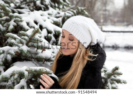 beautiful girl in the winter in the park near the Christmas tree in snow - stock photo