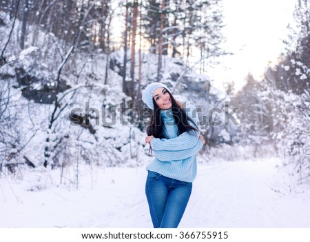 beautiful girl in the winter. the girl against snow branches. the girl rejoices to winter weather. the girl in the beautiful winter wood. the girl with a beautiful smile in the winter wood. - stock photo
