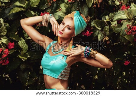 Beautiful girl in turban posing in the garden - stock photo