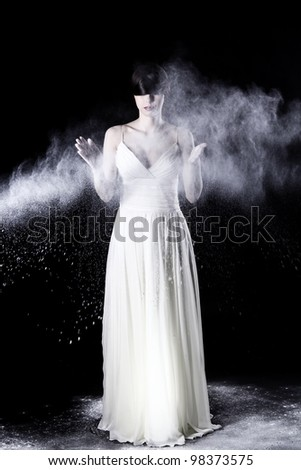 Beautiful girl in white dress and flying dust over black background - stock photo