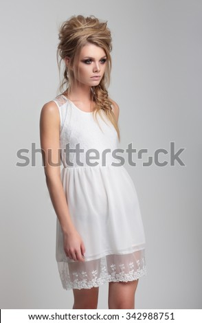 Beautiful girl in white dress goes on a light background. - stock photo
