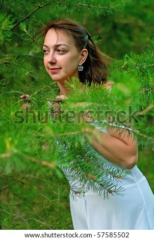 Beautiful girl in white dress in wood with pines. Shallow DOF