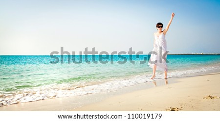 beautiful girl in white dress  on the beach raised her hand up - stock photo