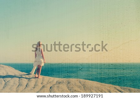 Beautiful girl in white dress standing on a rock and looking at the sea. Filtered image: vintage, grunge and texture effects - stock photo