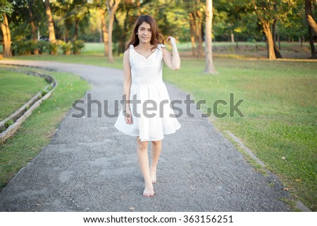 Beautiful girl in white dress walking barefoot on the partway in the park - stock photo