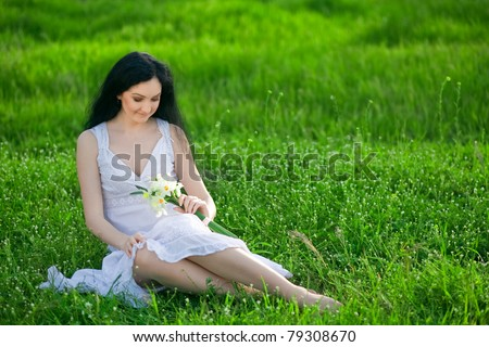 Beautiful girl in white sarafan sitting on the grass and smiles, European, White, Caucasian,