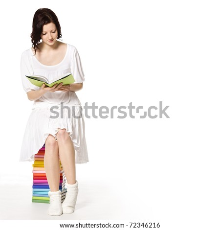 Beautiful girl in white sitting on colorful stack of books reading, isolated on white background and plenty of copy-space. - stock photo
