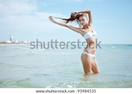 Beautiful girl in white swimsuit sunning on the sea - stock photo