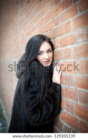 Beautiful girl in winter against a brick wall - stock photo