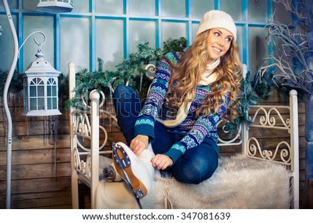 Beautiful girl in winter clothes puts on skates - stock photo