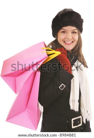 beautiful girl in winter coat carrying pink gift bags after a sale - stock photo