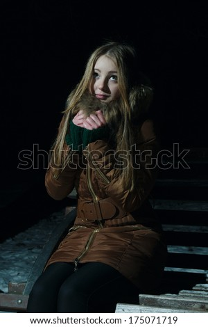 Beautiful girl in winter freezes on a wood bench