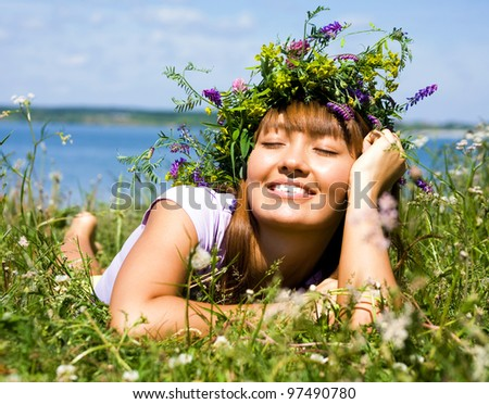 beautiful girl in wreath of flowers lay in meadow on sunny day - stock photo