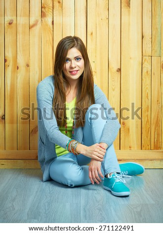 Beautiful girl in youth style dressed. Floor sitting woman.