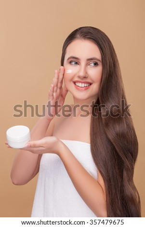 Beautiful girl is applying cream on her face. She is standing and smiling. The lady with long hair is wearing a white towel. Isolated - stock photo