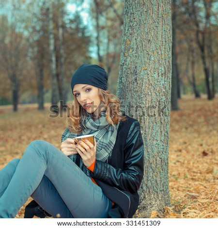 beautiful girl is drinking coffee in autumn park. Beautiful Happy Smiling autumn Woman with Mug Outdoor. Laughing Girl Outdoors with Hot Drink