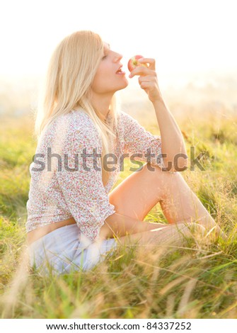 Beautiful girl is eating apple while sitting on green field - stock photo