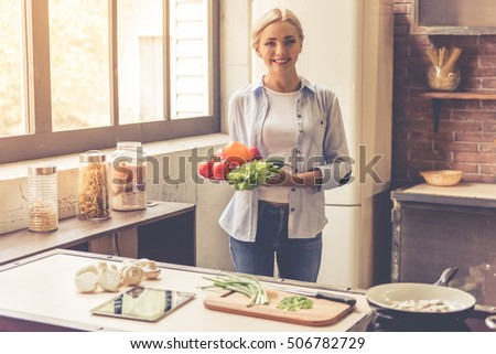 Beautiful girl is holding vegetables, looking at camera and smiling while cooking in kitchen at home