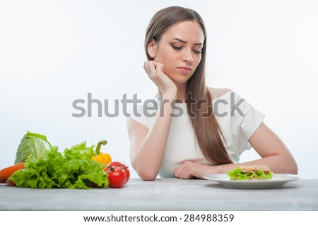 Beautiful girl is looking at hamburger with aversion. She is sitting at the table on which there are healthy vegetables are also situated. Isolated on a white background - stock photo