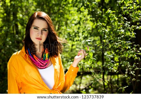 Beautiful girl is looking at the camera. Nature scene. - stock photo