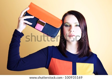 Beautiful girl is posing with bag. Focus on face. - stock photo