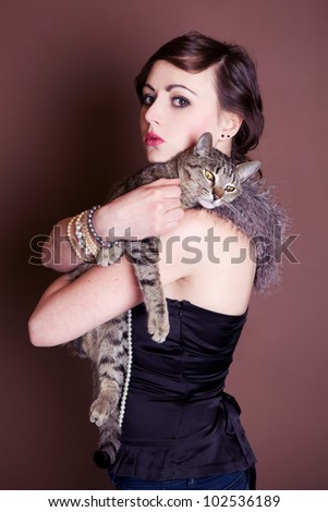 Beautiful girl is posing with cat. Focus on face. - stock photo