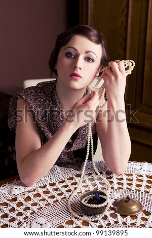 Beautiful girl is posing with pearls. Focus on face. Vintage shoot. - stock photo