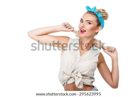 Beautiful girl is raising rolling-pin behind her neck. She is smiling and looking forward. Isolated on background and copy space in left side - stock photo