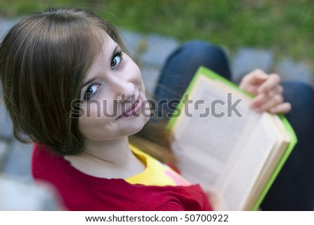 Beautiful girl is reading book. - stock photo